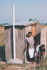 Courtest of WEDC, woman standing by latrine i Ghana